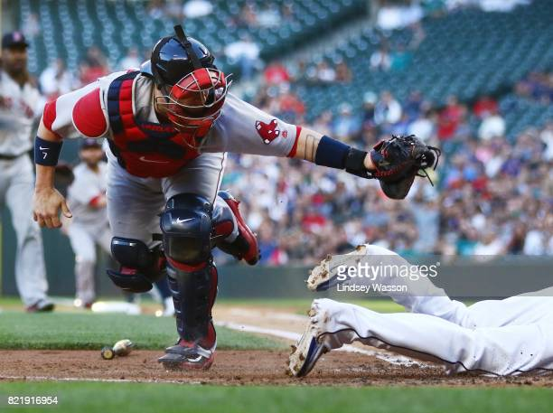 Christian Vazquez of the Boston Red Sox can't get the tag on Ben Gamel of the Seattle Mariners at home plate as he scores in the fourth inning at...