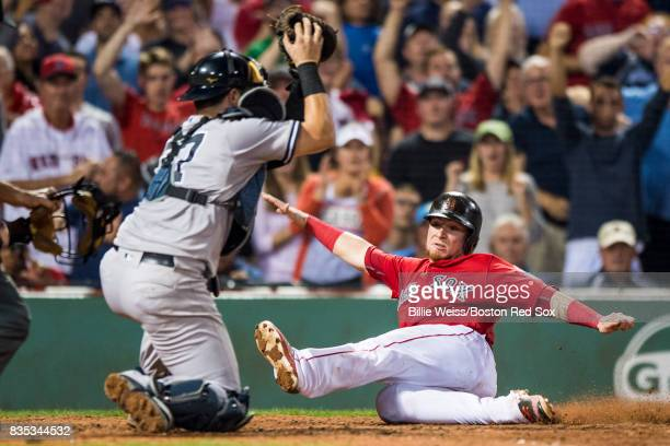 Christian Vazquez of the Boston Red Sox evades the tag of Gary Sanchez of the New York Yankees as he scores during the eighth inning of a game on...
