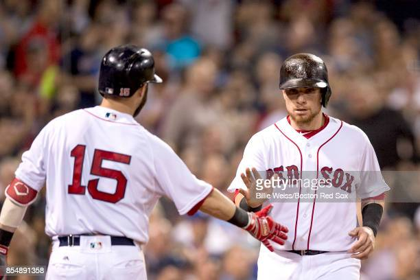 Christian Vazquez of the Boston Red Sox high fives Dustin Pedroia after scoring during the second inning of a game against the Toronto Blue Jays on...