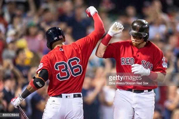 Christian Vazquez of the Boston Red Sox high fives Eduardo Nunez after hitting a solo home run during the fifth inning of a game against the New York...