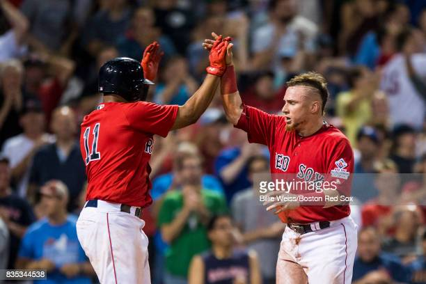 Christian Vazquez of the Boston Red Sox high fives Rafael Devers after scoring during the eighth inning of a game against the New York Yankees on...
