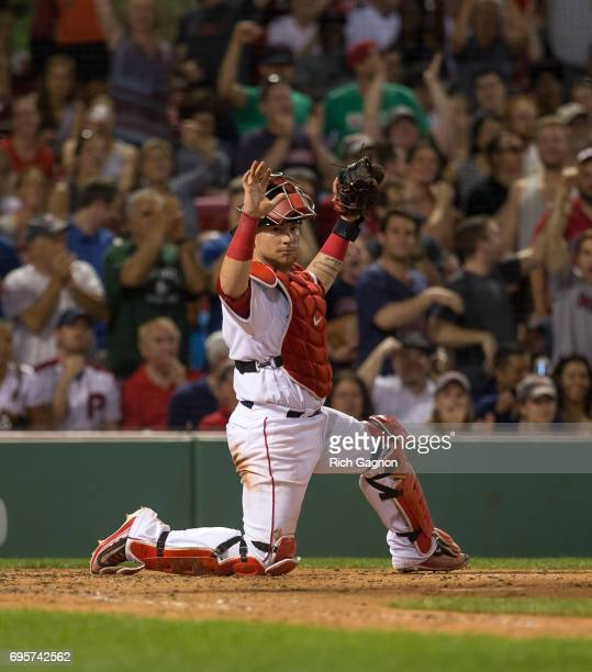 Christian Vazquez of the Boston Red Sox hold up the ball after he applied a tag for an out on Howie Kendrick of the Philadelphia Phillies on a throw...