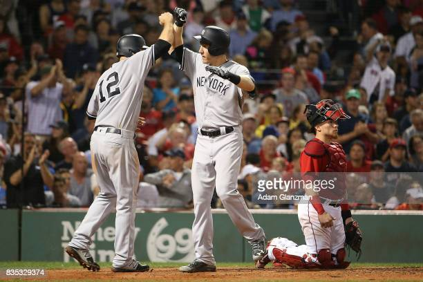 Christian Vazquez of the Boston Red Sox looks on as Todd Fraizer high fives Chase Headley of the New York Yankees after hitting a tworun home run in...