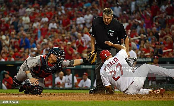 Christian Vazquez of the Boston Red Sox misses the tag as Jhonny Peralta of the St Louis Cardinals scores during the first inning at Busch Stadium on...