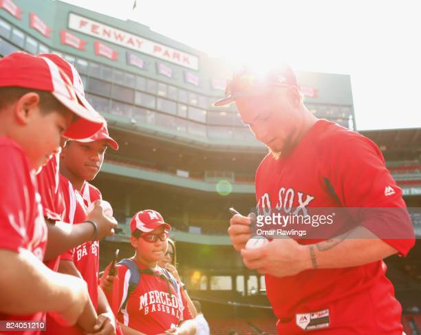 Christian Vazquez of the Boston Red Sox signs autographs for fans before the game against the Kansas City Royals at Fenway Park on July 28 2017 in...