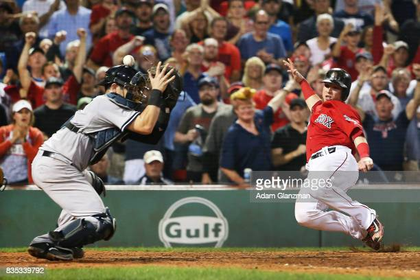 Christian Vazquez of the Boston Red Sox slides safely into home as the throw bounces off the helmet of Austin Romine of the New York Yankees in the...