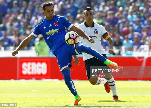 Christian Vilches of U De Chile fights for the ball with Esteban Paredes of Colo Colo during a match between U de Chile and Colo Colo as part of...