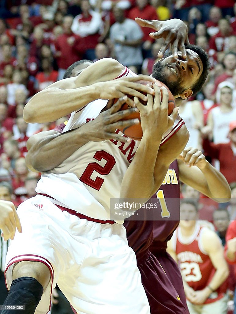 Christian Watford #2 of the Indiana Hoosiers and Trevor Mbakwe #32 of the Minnesota Golden Gophers reach for a loose ball during the game at Assembly Hall on January 12, 2013 in Bloomington, Indiana.