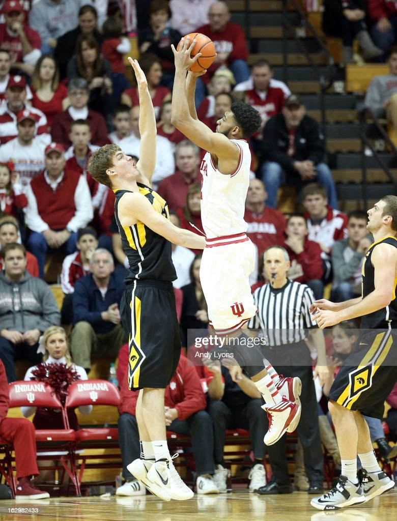 Christian Watford #2 of the Indiana Hoosiers shoots the ball while defended by Adam Woodbury #34 of the Iowa Hawkeyes during the game at Assembly Hall on March 2, 2013 in Bloomington, Indiana.