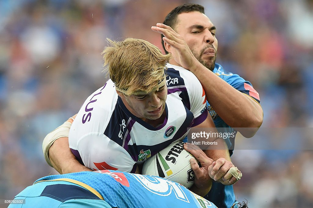 Christian Welch of the Storm is tackled by Ryan James and Leivaha Pulu of the Titans during the round nine NRL match between the Gold Coast Titans and the Melbourne Storm on May 1, 2016 in Gold Coast, Australia.