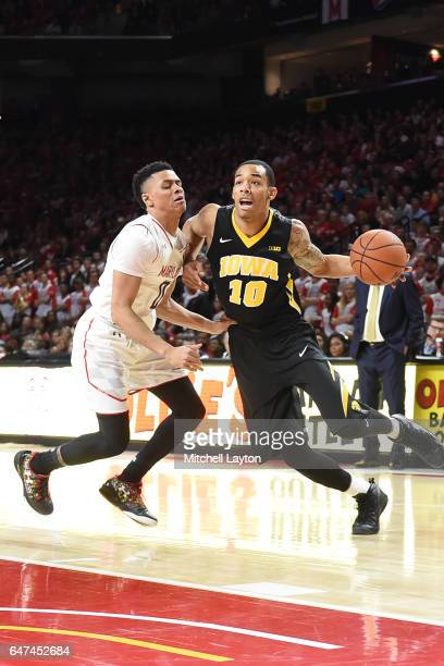 Christian Williams of the Iowa Hawkeyes dribbles around Anthony Cowan of the Maryland Terrapins during a college basketball game at the XFinity...