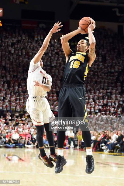 Christian Williams of the Iowa Hawkeyes takes a shot over Anthony Cowan of the Maryland Terrapins during a college basketball game at the XFinity...