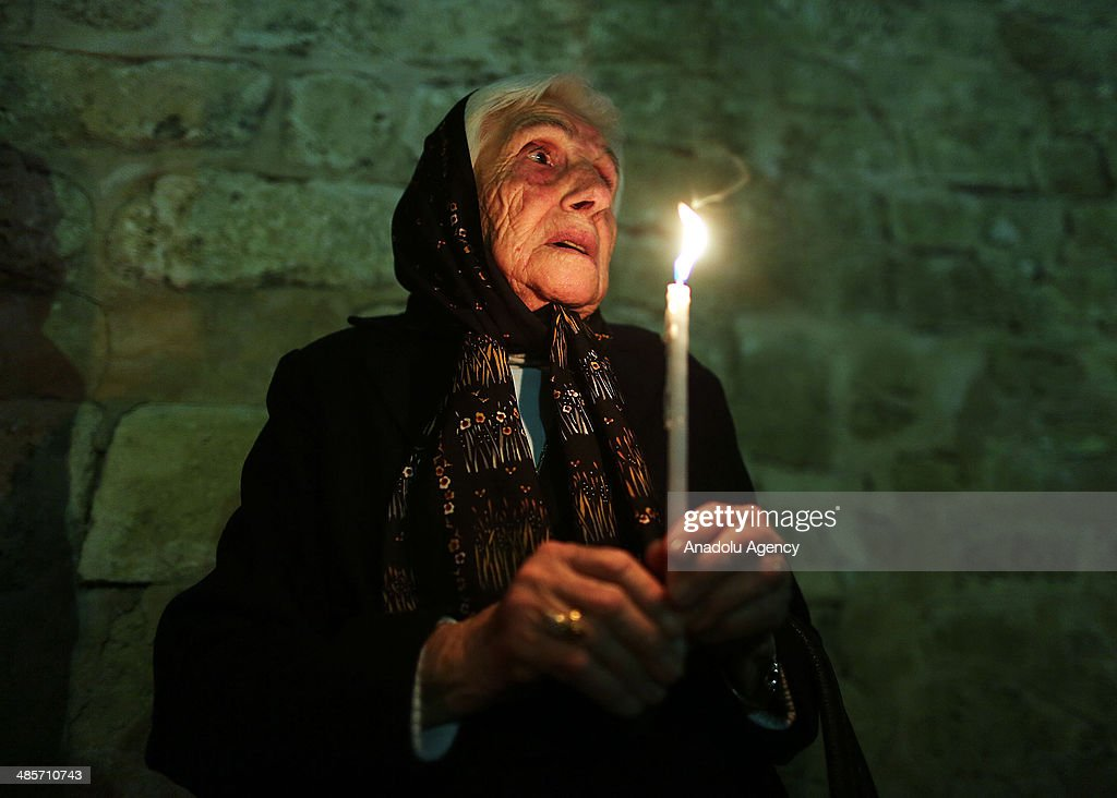 A Christian woman holds a candle during the Easter Celebration ceremony in Saint Porphyrius Orthodox Christian church of Gaza on April 19, 2014.