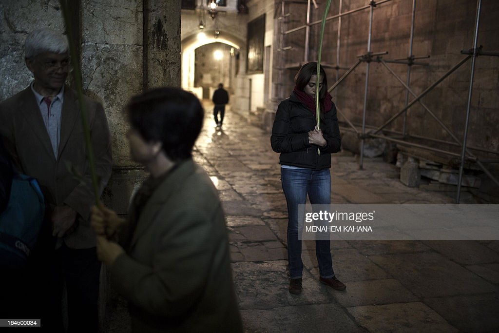 A Christian woman prays while holding a palm branch during the Palm Sunday procession at the Church of the Holy Sepulchre in Jerusalem's old city on March 24, 2013. Palm Sunday marks the triumphant return of Jesus Christ to Jerusalem when a cheering crowd greeted him waving palm leaves, a week before his crucifixion. AFP PHOTO/MENAHEM KAHANA
