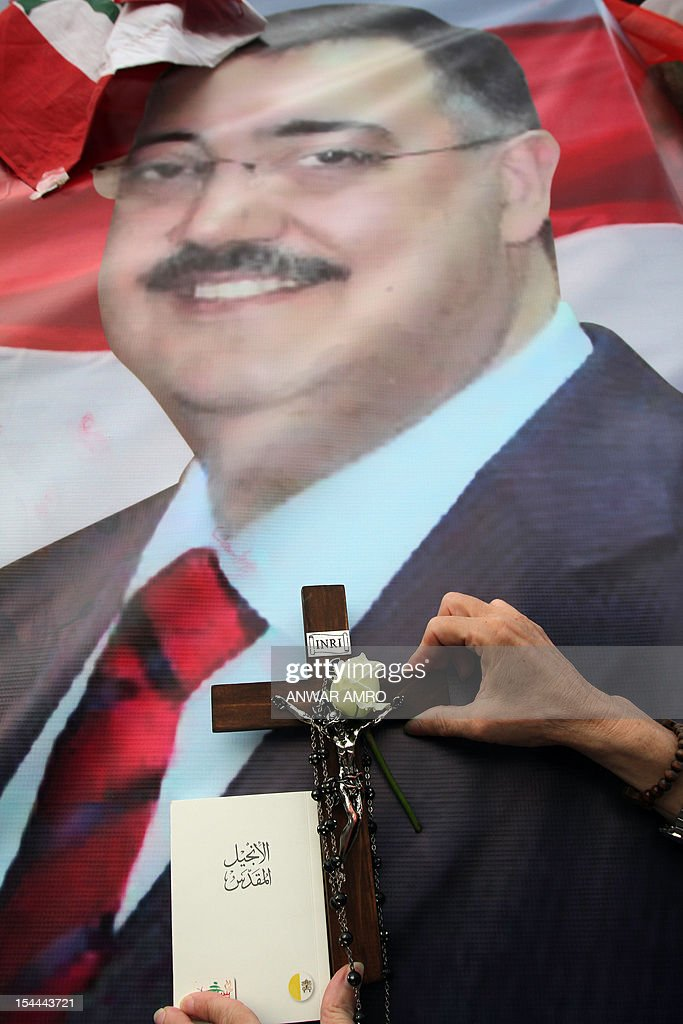 A Christian woman uses a cross and a rosary to bless a poster with an image of Internal Security Forces (ISF) intelligence chief General Wissam al-Hassan, during a protest against his killing in Martyrs' Square in downtown Beirut, on October 20, 2012. Lebanon was reeling the day after Hassan was killed in a bombing that was blamed on Syria and also raised fears the country is being sucked into the war ravaging its neighbour.