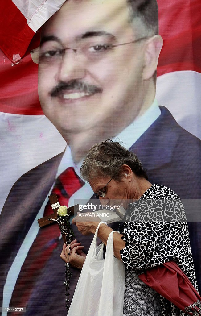 A Christian woman uses a cross and a rosary to bless a poster with an image of Internal Security Forces (ISF) intelligence chief General Wissam al-Hassan, during a protest against his killing in Martyrs' Square in downtown Beirut, on October 20, 2012. Lebanon was reeling the day after Hassan was killed in a bombing that was blamed on Syria and also raised fears the country is being sucked into the war ravaging its neighbour. AFP PHOTO /ANWAR AMRO