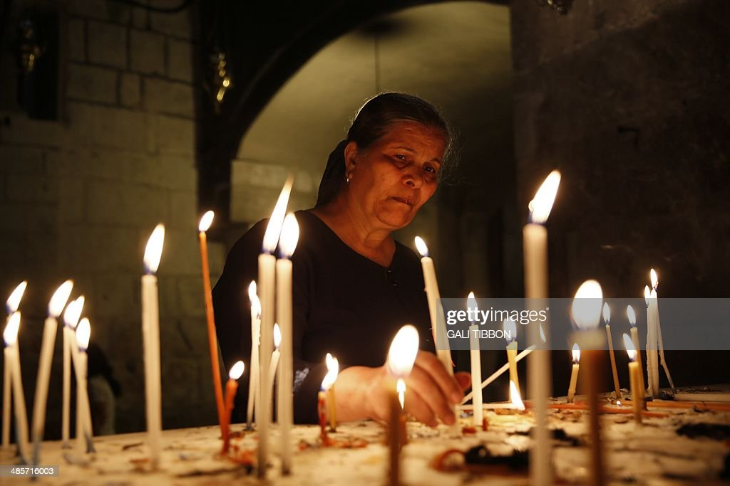 A Christian worshiper lights a candle during Easter Sunday mass in the Church of Holy Sepulchre in Jerusalem's Old City on April 20, 2014. Thousands of Christian pilgrims thronged the Church of the Holy Sepulchre in Jerusalem's Old City amid tight security to celebrate Easter. AFP PHOTO/GALI TIBBON