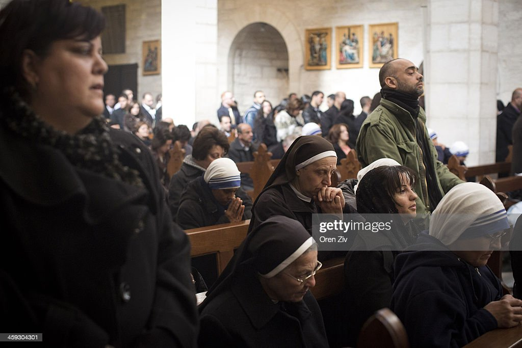 Christian worshipers and nuns pray during a Christmas mass at the Church of the Nativity on December 25, 2013 in Bethlehem, West Bank. Every Christmas pilgrims travel to the church where a gold star embedded in the floor marks the spot where Jesus was believed to have been born.