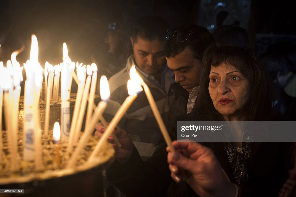 Christian worshipers light candels the Church of the Nativity, traditionally believed to be the birthplace of Jesus Christ, on December 25, 2013 in Bethlehem, West Bank. Every Christmas pilgrims travel to the church where a gold star embedded in the floor marks the spot where Jesus was believed to have been born.