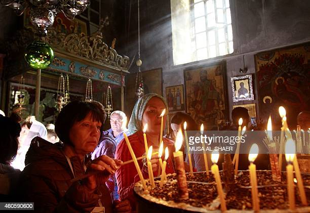 Christian worshipers light candles at the Church of the Nativity revered as the site of Jesus Christ's birth in the West Bank town of Bethlehem on...