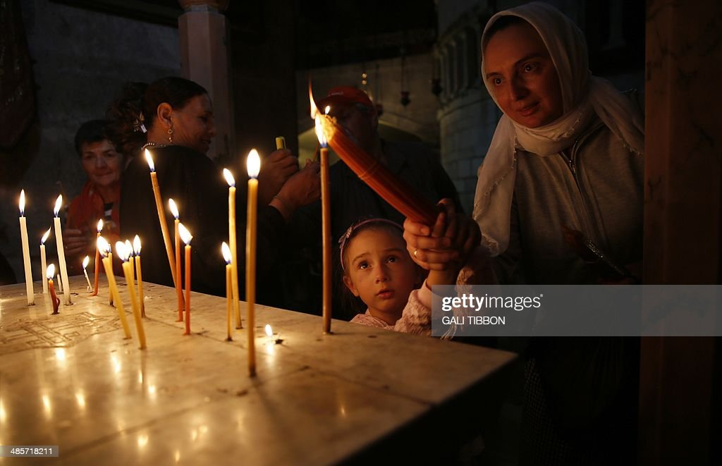 Christian worshipers light candles during Easter Sunday mass in the Church of Holy Sepulchre in Jerusalem's Old City on April 20, 2014. Thousands of Christian pilgrims thronged the Church of the Holy Sepulchre in Jerusalem's Old City amid tight security to celebrate Easter.