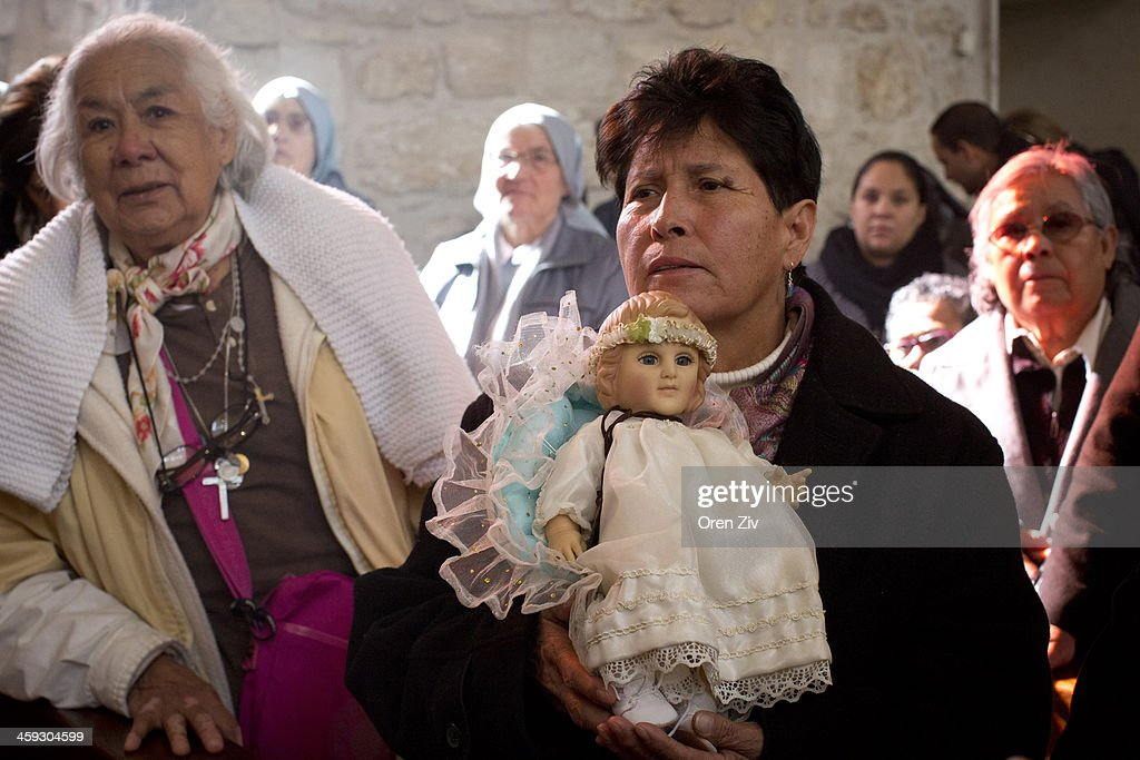 A Christian worshipper holds a Baby Jesus doll during Christmas mass at the Church of the Nativity on December 25, 2013 in Bethlehem, West Bank. Every Christmas pilgrims travel to the church where a gold star embedded in the floor marks the spot where Jesus was believed to have been born.