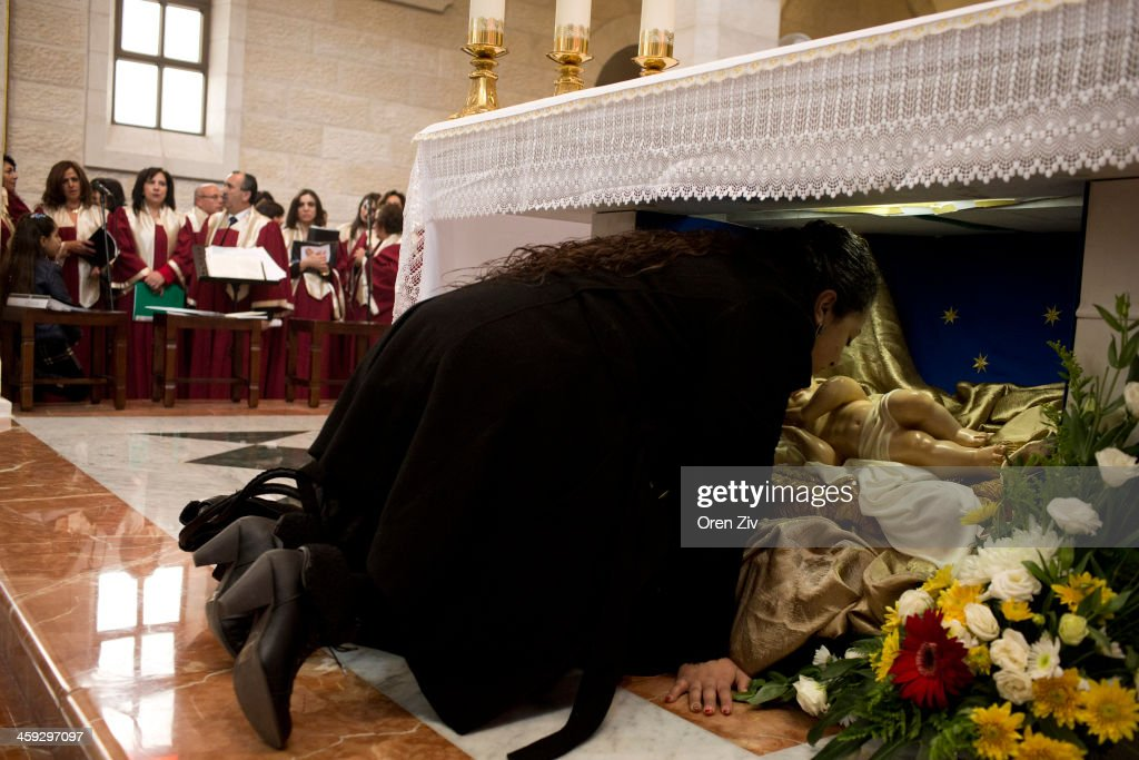 A Christian worshipper kisses a Baby Jesus statue at the altar during the Christmas mass at the Church of the Nativity on December 25, 2013 in Bethlehem, West Bank. Every Christmas pilgrims travel to the church where a gold star embedded in the floor marks the spot where Jesus was believed to have been born.