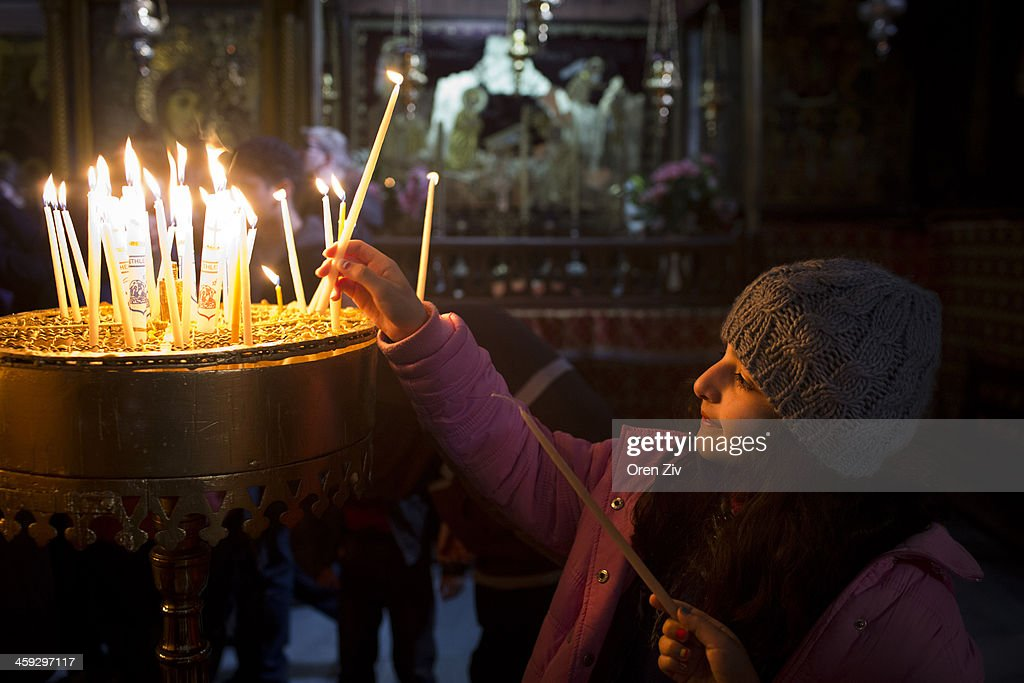 A Christian worshipper lights candles at the Church of the Nativity on December 25, 2013 in Bethlehem, West Bank. Every Christmas pilgrims travel to the church where a gold star embedded in the floor marks the spot where Jesus was believed to have been born.