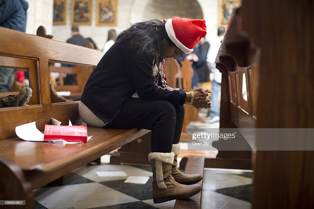 A Christian worshipper prays during the Christmas mass at the Church of the Nativity on December 25, 2013 in Bethlehem, West Bank. Every Christmas pilgrims travel to the church where a gold star embedded in the floor marks the spot where Jesus was believed to have been born.