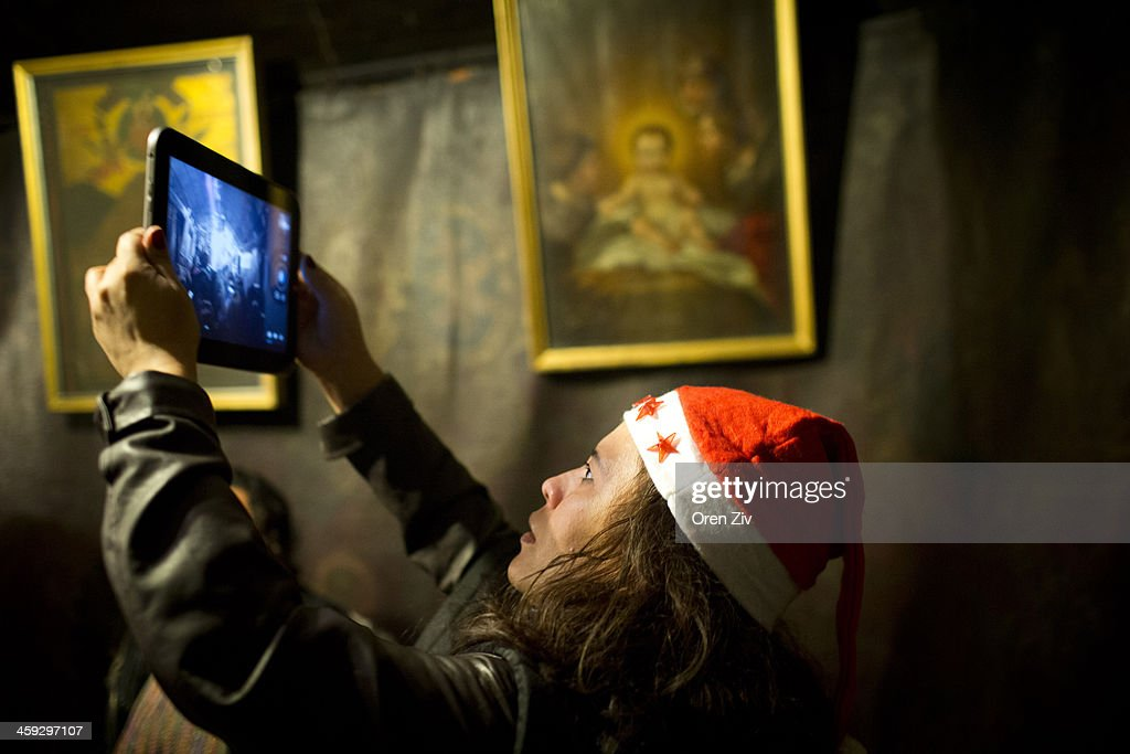 A Christian worshipper uses her ipad to take photos at the Grotto at the Church of the Nativity on December 25, 2013 in Bethlehem, West Bank. Every Christmas pilgrims travel to the church where a gold star embedded in the floor marks the spot where Jesus was believed to have been born.