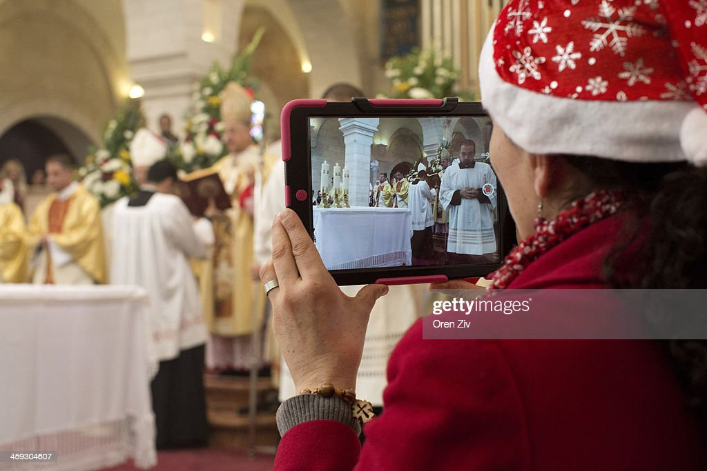 A Christian worshipper uses her iPad to take photos during a Christmas mass at the Church of the Nativity on December 25, 2013 in Bethlehem, West Bank. Every Christmas pilgrims travel to the church where a gold star embedded in the floor marks the spot where Jesus was believed to have been born.