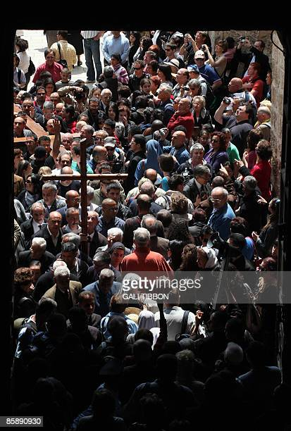 Christian worshippers carry a cross along the Via Dolorosa in Jerusalem's old city as they enter the Church of the Holy Sepulchre during the Good...