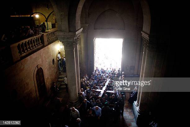 Christian worshippers carry a large wooden cross into the Church of the Holy Sepulchre after the Good Friday procession along the Via Dolorosa on...