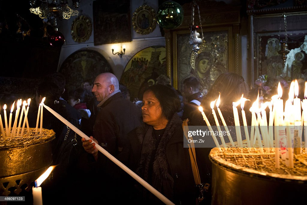 Christian worshippers light candles at the Church of the Nativity on December 25, 2013 in Bethlehem, West Bank. Every Christmas pilgrims travel to the church where a gold star embedded in the floor marks the spot where Jesus was believed to have been born.
