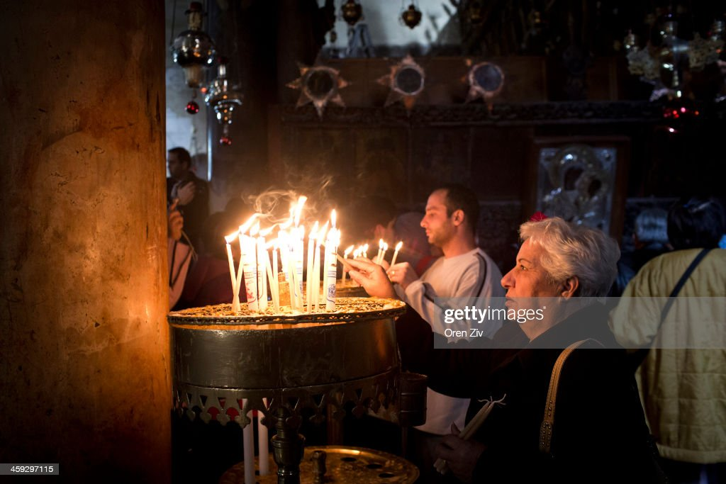 Christian worshippers lights candles at the Church of the Nativity on December 25, 2013 in Bethlehem, West Bank. Every Christmas pilgrims travel to the church where a gold star embedded in the floor marks the spot where Jesus was believed to have been born.