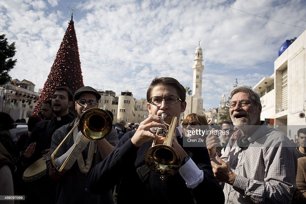 Christian worshippers play music as the enter the Church of the Nativity on December 25, 2013 in Bethlehem, West Bank. Every Christmas pilgrims travel to the church where a gold star embedded in the floor marks the spot where Jesus was believed to have been born.