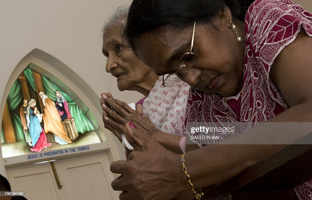 Christian worshippers pray in front of a window panel, which has an image resembling the Virgin Mary, at the Church of Our Lady of Lourdes, at the port town of Klang, on the outskirts of Kuala Lumpur on November 20, 2012. The window pane at a Malaysian hospital which has an image resembling the Virgin Mary has been moved to the church after it attracted large number of worshippers. AFP PHOTO / Saeed KHANlarge number of worshippers. AFP PHOTO / Saeed KHAN
