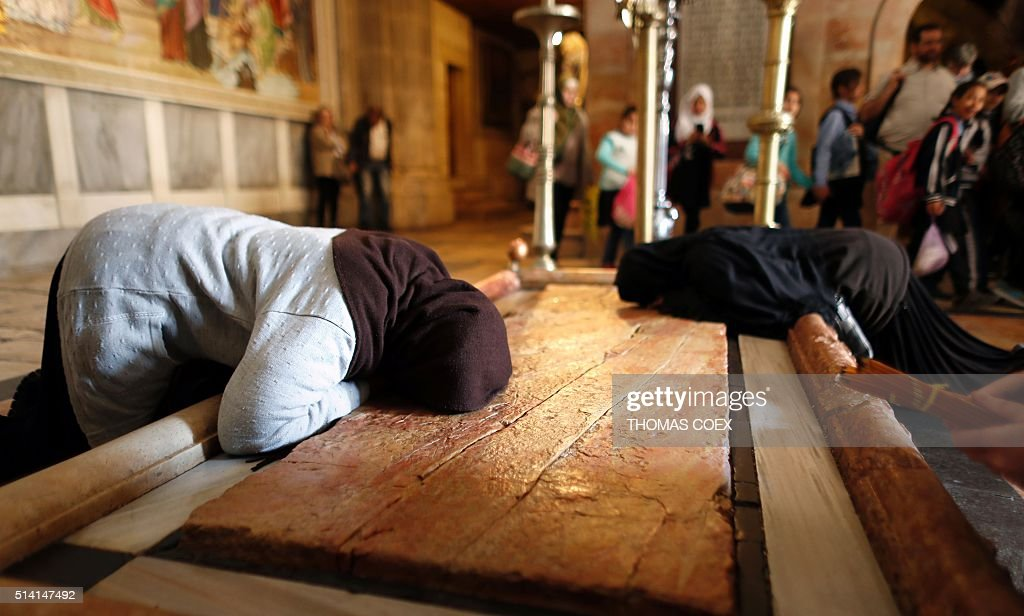 Christian worshippers pray on the Stone of the Anointing inside the Church of the Holy Sepulchre in Jerusalem's Old City on March 7 2016 / AFP /...