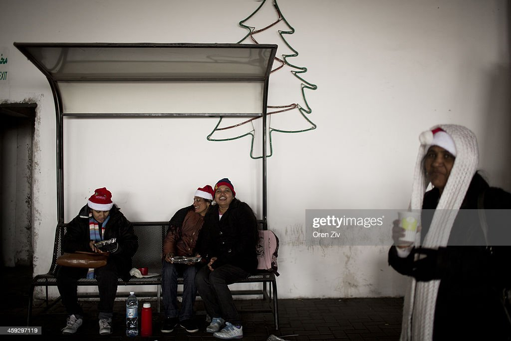 Christian worshippers sit in a parking lot near the Church of the Nativity on December 25, 2013 in Bethlehem, West Bank. Every Christmas pilgrims travel to the church where a gold star embedded in the floor marks the spot where Jesus was believed to have been born.