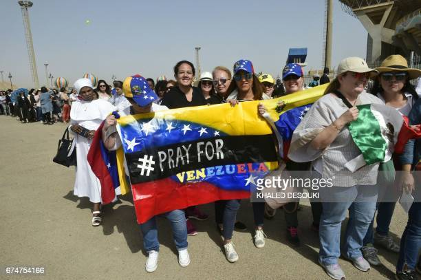 Christian worshippers wave a Venezuelan flag as they queue to attend a mass led by Pope Francis on April 29 2017 at a stadium in the Egyptian capital...
