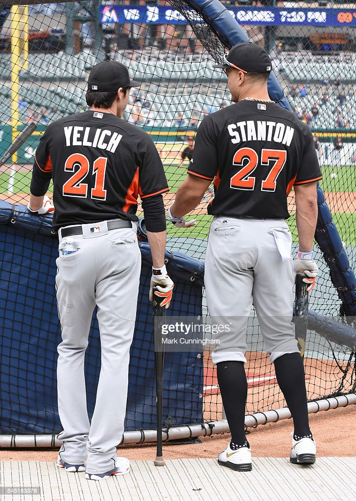 Christian Yelich and Giancarlo Stanton of the Miami Marlins stand together at the batting cage during batting practice prior to the game against the...