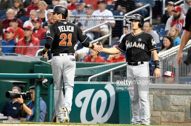 Christian Yelich and JT Realmuto of the Miami Marlins celebrate after scoring in the first inning against the Washington Nationals at Nationals Park...