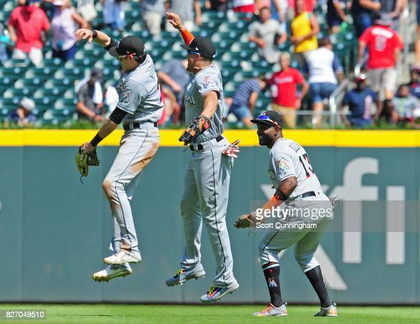 Christian Yelich Marcell Ozuna and Giancarlo Stanton of the Miami Marlins celebrate after the game against the Atlanta Braves at SunTrust Park on...