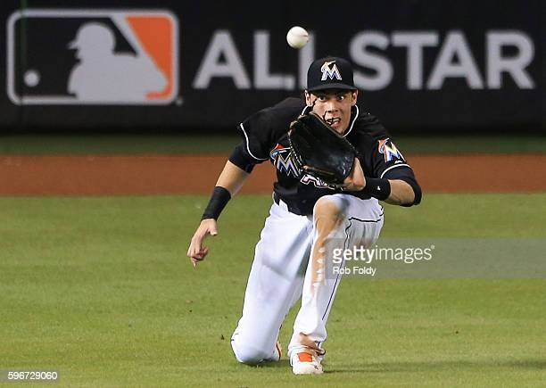 Christian Yelich of the Miami Marlins catches a fly ball in the outfield during the game against the San Diego Padres at Marlins Park on August 27...