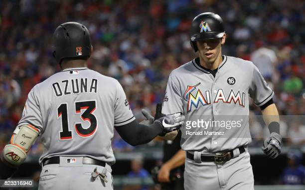 Christian Yelich of the Miami Marlins celebrates a threerun homerun with Marcell Ozuna against the Texas Rangers in the fifth inning at Globe Life...