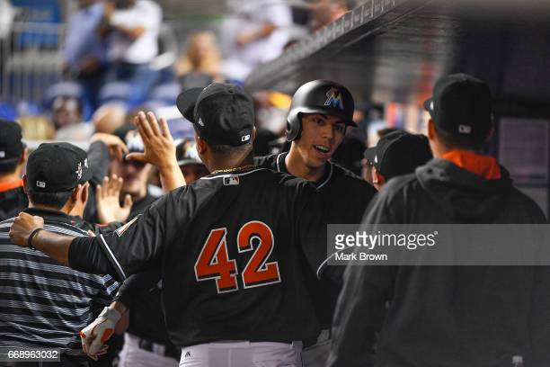 Christian Yelich of the Miami Marlins celebrates in the dugout after he hit a a 2 run homer eighth inning during the game between the Miami Marlins...