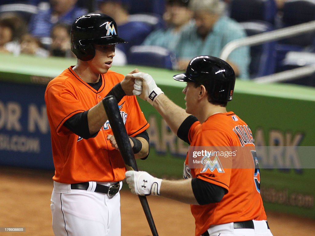 Christian Yelich #21 of the Miami Marlins celebrates with teammate Logan Morrison after hitting an RBI triple in the second inning against the Loos Angeles Dodgers at Marlins Park on August 19, 2013 in Miami, Florida.
