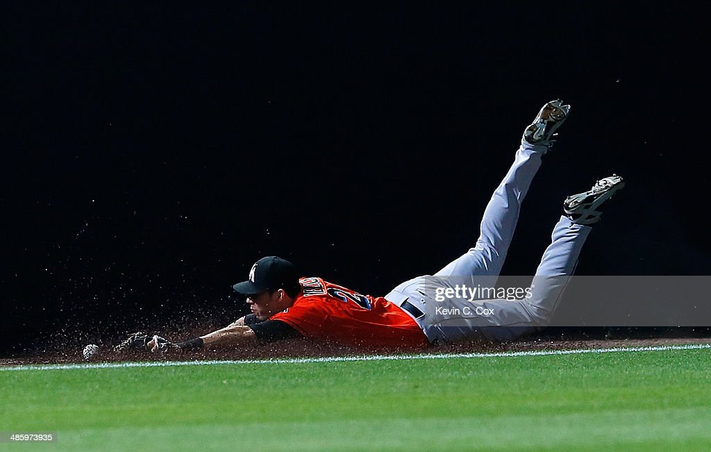 <a gi-track='captionPersonalityLinkClicked' href=/galleries/search?phrase=Christian+Yelich&family=editorial&specificpeople=9527291 ng-click='$event.stopPropagation()'>Christian Yelich</a> #21 of the Miami Marlins drops a double hit by Jordan Schafer #17 of the Atlanta Braves in the ninth inning at Turner Field on April 21, 2014 in Atlanta, Georgia.