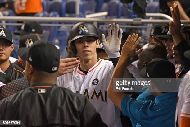 Christian Yelich of the Miami Marlins high fives teammates in the dugout after hitting a home run in the first inning against the Arizona...