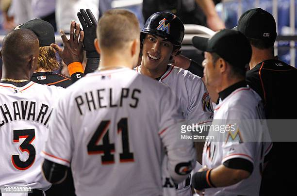 Christian Yelich of the Miami Marlins is congratulated after hitting a two run home run during a game against the San Diego Padres at Marlins Park on...